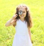 Niño de la niña que mira a través de una lupa en la naturaleza Imagen de archivo libre de regalías