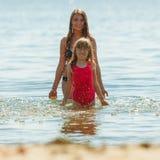 Niño de la niña y madre de la mujer en agua de mar Diversión Foto de archivo