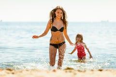 Niño de la niña y madre de la mujer en agua de mar Diversión Fotografía de archivo libre de regalías