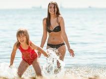 Niño de la niña y madre de la mujer en agua de mar Diversión Imagen de archivo
