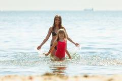 Niño de la niña y madre de la mujer en agua de mar Diversión Foto de archivo libre de regalías