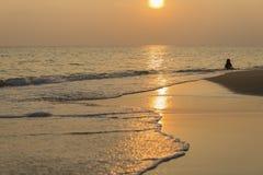 Niño de la silueta en la playa en la puesta del sol Foto de archivo libre de regalías