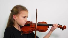Niño de la vista lateral que toca el violín, tiro del estudio metrajes