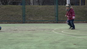 Niño de los deportes Muchacha que juega a fútbol Bebé con la bola en campo de deportes almacen de metraje de vídeo