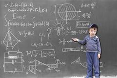 Niño de menor importancia en las fórmulas de la escritura de la pizarra imagen de archivo libre de regalías