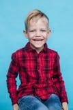 Niño de moda con la camisa roja Moda estilo Retrato del estudio sobre fondo azul Imagenes de archivo