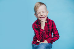 Niño de moda con la camisa roja Moda estilo Retrato del estudio sobre fondo azul Fotos de archivo