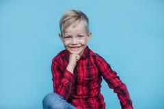 Niño de moda con la camisa roja Moda estilo Retrato del estudio sobre fondo azul Fotografía de archivo libre de regalías