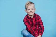 Niño de moda con la camisa roja Moda estilo Retrato del estudio sobre fondo azul Fotos de archivo libres de regalías