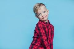 Niño de moda con la camisa roja Moda estilo Retrato del estudio sobre fondo azul Imagen de archivo