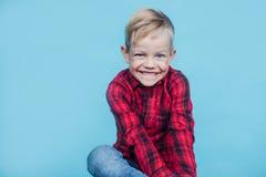 Niño de moda con la camisa roja Moda estilo Retrato del estudio sobre fondo azul Foto de archivo libre de regalías