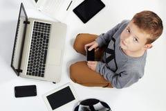 Niño de moda con los ordenadores, tabletas, teléfonos, artilugios alrededor Imagen de archivo