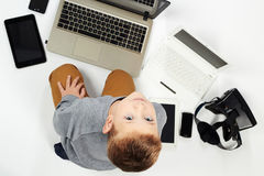 Niño de moda con los ordenadores, tabletas, teléfonos, artilugios alrededor Fotografía de archivo