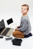 Niño de moda con los ordenadores, tabletas, teléfonos, artilugios alrededor Fotos de archivo