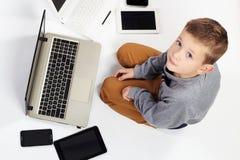 Niño de moda con los ordenadores, tabletas, teléfonos, artilugios alrededor Imagenes de archivo