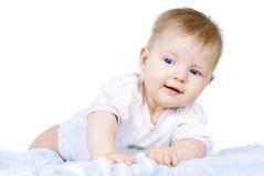 Niño de ojos azules que miente en un fondo blanco fotografía de archivo libre de regalías