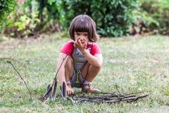 Niño de pensamiento que juega con los palillos de madera en parque verde Imágenes de archivo libres de regalías