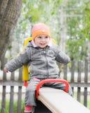 Niño de risa en el oscilación Foto de archivo libre de regalías