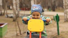 Niño de risa que oscila en un eje de balancín almacen de metraje de vídeo