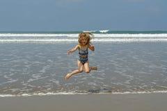 Niño de salto en la playa Imagenes de archivo
