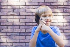 Niño de Smilig que habla en gente del teléfono celular, tecnología y concepto de la comunicación Imagen de archivo