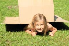 Niño debajo de la caja Imagen de archivo