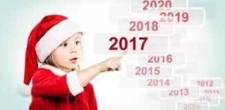 Niño del Año Nuevo en Santa Hat La Navidad y nuevo Year& x27; s Eve Fotos de archivo