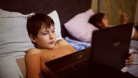 Niño del adolescente que juega el ordenador portátil de los juegos de ordenador almacen de video