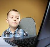 Niño del apego del ordenador con el cuaderno del ordenador portátil Imagenes de archivo