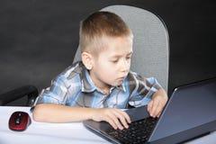 Niño del apego del ordenador con el cuaderno del ordenador portátil Foto de archivo libre de regalías