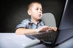 Niño del apego del ordenador con el cuaderno del ordenador portátil Fotografía de archivo