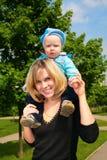 Niño del asimiento de la madre en los hombros al aire libre Imágenes de archivo libres de regalías