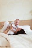Niño del bebé con la mamá que juega en una cama debajo de una manta, Fotos de archivo libres de regalías