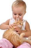 Niño del bebé que juega con un gatito Imagen de archivo libre de regalías