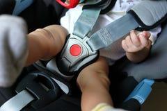 Niño del bebé que se sienta en asiento de carro con el cinturón de seguridad cerrado Fotos de archivo libres de regalías