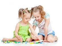 Niño del entrenamiento de una más vieja hermana para realizar el juguete del mosaico Foto de archivo
