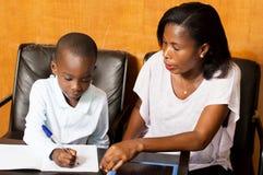 Niño del estudiante con su madre en casa Foto de archivo libre de regalías