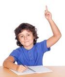 Niño del estudiante que estudia levantando la mano Foto de archivo
