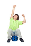 Niño del ganador que se sienta en balón de fútbol azul imagen de archivo libre de regalías