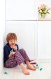 Niño del gusto por lo dulce que oculta en la esquina de la cocina, comiendo los caramelos fotos de archivo libres de regalías