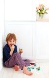 Niño del gusto por lo dulce que oculta en la esquina de la cocina, comiendo los caramelos imágenes de archivo libres de regalías