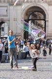 Niño del hombre y de la niña con las burbujas de jabón grandes Fotos de archivo