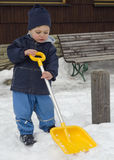 Niño del invierno con la pala de la nieve Imagen de archivo