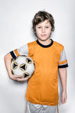Niño del jugador de fútbol en uniforme de la naranja con la bola Foto de archivo