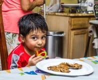 Niño del Latino que se sienta en una tabla con la comida Imagen de archivo libre de regalías