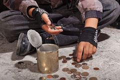 Niño del mendigo que cuenta las monedas que se sientan en piso concreto dañado Imagen de archivo libre de regalías