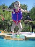 Niño del Mid-Air que se divierte en la piscina Foto de archivo