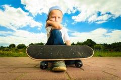 Niño del muchacho del patinador con su monopatín Actividad al aire libre fotografía de archivo libre de regalías