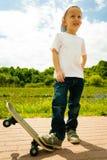 Niño del muchacho del patinador con su monopatín Actividad al aire libre foto de archivo