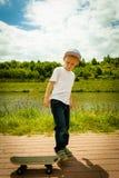 Niño del muchacho del patinador con su monopatín Actividad al aire libre imagenes de archivo